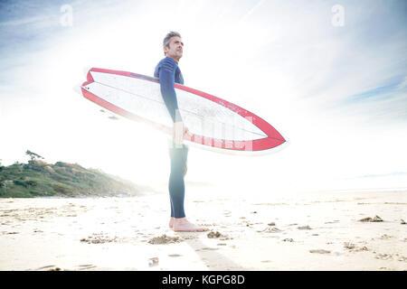 Surfer sulla spiaggia tenendo la tavola da surf, per entrare in acqua Foto Stock