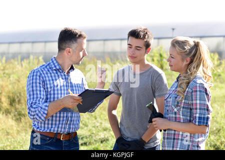 Giovani con istruttore in campo agricolo Foto Stock