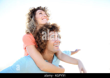 L uomo dando piggyback ride alla ragazza sulla spiaggia Foto Stock