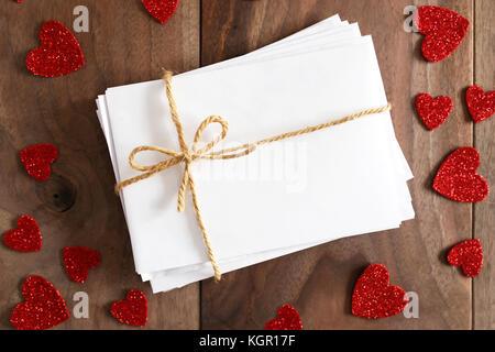 Un pacco di lettere di amore nel bianco buste bianche legata con lo spago stringa prua è seduto su un rustico di legno di ciliegio listone tabella, circondato da Valentine lui Foto Stock
