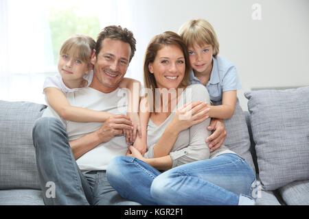 La famiglia felice rilassante sul lettino a casa Foto Stock