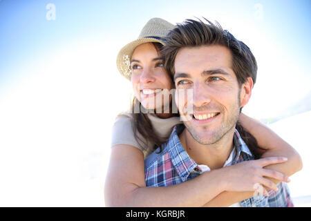 L uomo dando piggyback ride per ragazza in spiaggia Foto Stock