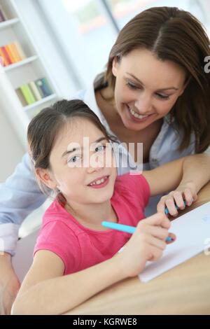 Scuola della bambina con la madre imparare a scrivere Foto Stock