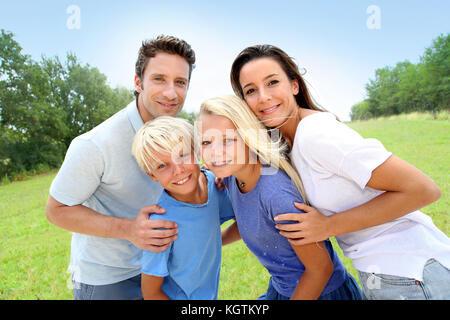 Ritratto fo famiglia felice in piedi in un paesaggio naturale Foto Stock