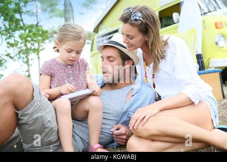 La famiglia a giocare con i video game in campeggio Foto Stock