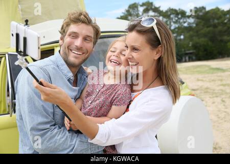Famiglia in piedi di fronte a camper van tenendo selfie foto Foto Stock
