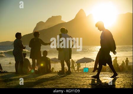 Rio de Janeiro - marzo 20, 2017: le persone si sono riunite a guardare il tramonto a arpoador, una popolare attività estiva per i turisti e la gente del posto.
