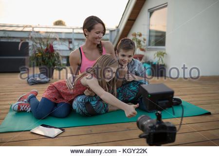 Madre e bambini con riprese con la videocamera, vlogging sul materassino yoga sul ponte patio Foto Stock