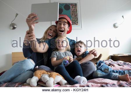 Famiglia giovane tenendo selfie con tavoletta digitale sul letto Foto Stock