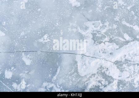 Screpolature sulla superficie del ghiaccio del fiume. Foto Stock