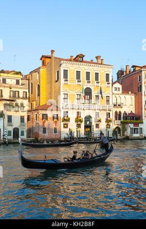 Serata romantica fila in gondola sul Canal Grande, Cannaregio, Venezia, Italia al tramonto con tre gondole di fronte Ca Civran e Casa Perducci.