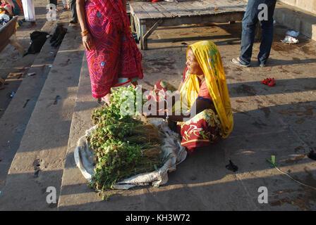 Una Donna vestita di un Sari vendere sul lungomare di Varanasi, Uttar Pradesh, India Foto Stock