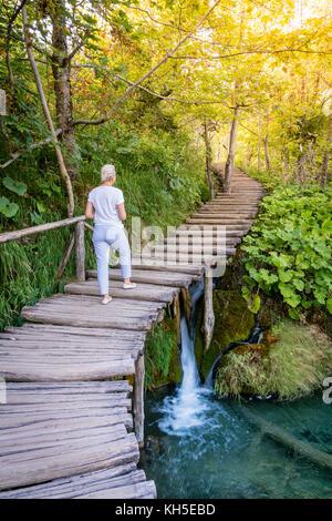 La donna è escursionismo su una passerella trail nel parco nazionale dei laghi di Plitvice, Croazia Foto Stock