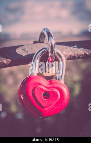 Simbolo dell'amore. vintage card con cuore rosso sfondo. Serratura metallica sul ponte di amanti. Foto Stock