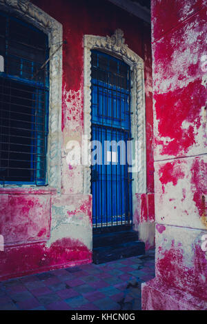 Peeling rosse pareti dipinte di blu e porta a una proprietà sul Malecon Havana, Cuba Foto Stock