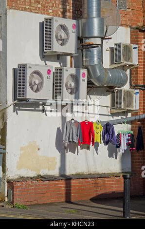 Una parete esterna di unità di condizionamento dell'aria con una linea di coloratissimi lavaggio asciugatura sotto, Foto Stock