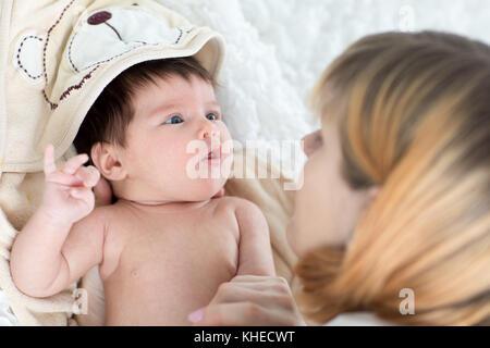 Felice madre e il suo bambino neonato cercando ciascuno ad altri Foto Stock