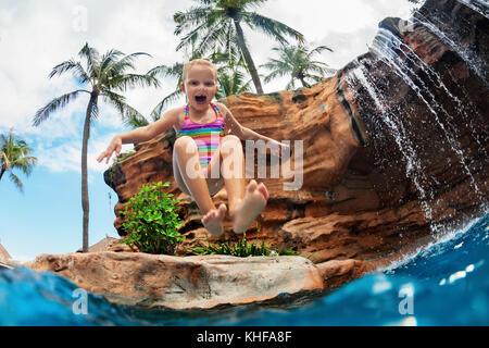 Bambino divertente imparare a nuotare con divertimento. ragazza jumping alta con spruzzi di acqua in piscina sotto Foto Stock