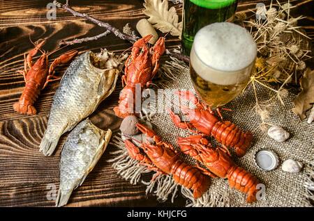 La birra con schiuma in vetro e asciugato il pesce salato e con bolliti gambero rosso su tela,giacente sul buio di pannelli di legno