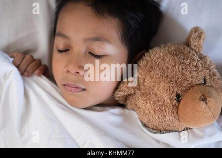Bambino addormentato sul letto con Orsacchiotto bianco e cuscino fogli.boy addormentarsi in mattinata.concetto del Foto Stock