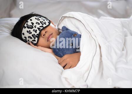 Bambino addormentato sul letto con Teddy bear cuscino bianco e fogli di indossare la maschera di sospensione.boy Foto Stock
