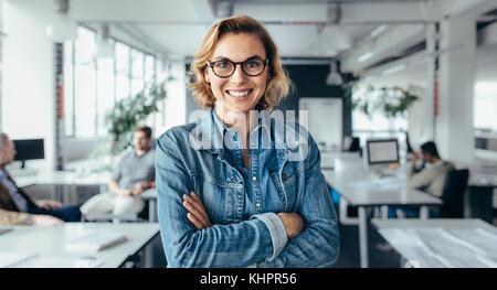 Felice executive femmina in piedi con le braccia incrociate. Giovane imprenditrice in piedi in ufficio. Foto Stock