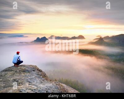 Momento di solitudine su esposta vetta rocciosa. man in black godono di una vista meravigliosa. escursionista sedersi Foto Stock