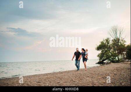 Incinta giovane passeggiando lungo la spiaggia con toddler maschio figlio, Lago Ontario, Canada Foto Stock