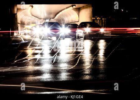 Sfocato il traffico notturno di pioggia per le strade delle città. vetture accodate all'uscita del tunnel in attesa Foto Stock