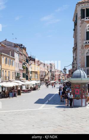Ingresso di Via Giuseppe Garibaldi, Castello, Venezia, Italia con turisti di pranzare in ristoranti all'aperto e Foto Stock