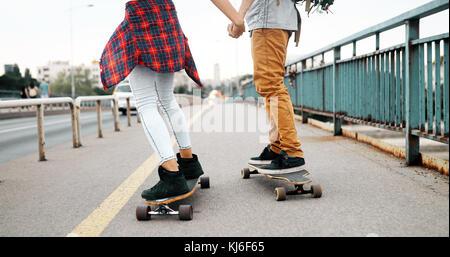 Giovane coppia attraente skateboard equitazione e divertimento Foto Stock