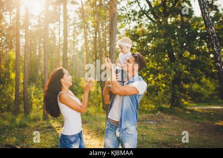 Elegante giovane famiglia mamma, papà e la figlia di un anno di età bionda seduta con il padre sulle spalle giocando Foto Stock