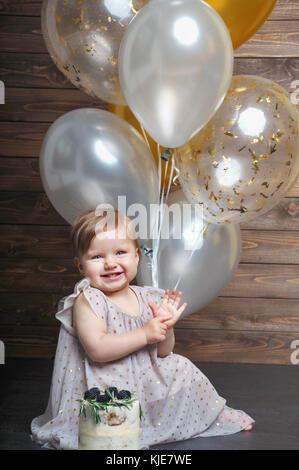 Happy Baby girl con aria palloni e sulla torta di compleanno. festa di famiglia del bambino. Un anno partito. carino infantile con gruppo di sfere Foto Stock