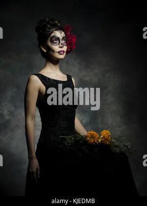 Messicano bella donna americana celebra Día de los Muertos ( Día de Muertos ) è la vacanza messicana noto anche come il Giorno dei Morti con cranio trucco e Roses nello stile di Catrina. Foto Stock