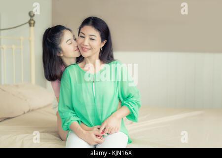 Asian amore di madre e figlia. donna felice in camera da letto con copia spazio. di età compresa tra la donna e Foto Stock