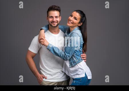 Una bella coppia giovane e abbraccia la tenuta di ciascun altro in studio Foto Stock