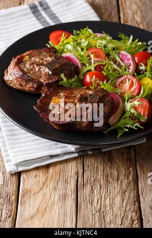 Deliziosa bistecca di agnello e insalata di verdure da ravanelli, pomodori e lattuga close-up su una piastra verticale. Foto Stock