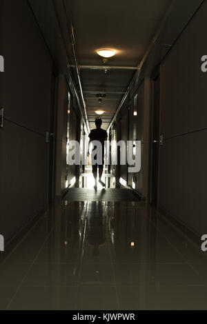 Uomo che cammina verso il basso un lungo corridoio Foto Stock