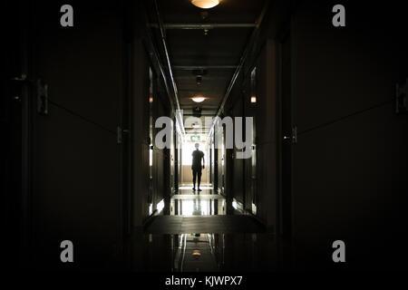 Uomo che cammina verso il basso un lungo corridoio scuro Foto Stock