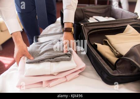 Close up di un irriconoscibile imprenditore valigia di imballaggio per il viaggio di lavoro abiti di piegatura su Foto Stock