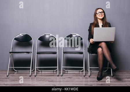 Sorridente giovane lavoratore di ufficio donna seduta sul pavimento di legno sedia utilizzando mobile computer portatile Foto Stock