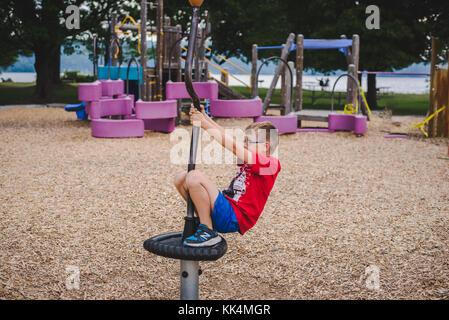 Un bambino gioca sul parco giochi in un giorno di estate Foto Stock