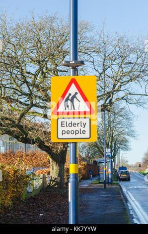 Segno di avvertimento di anziani attraversando la strada Foto Stock