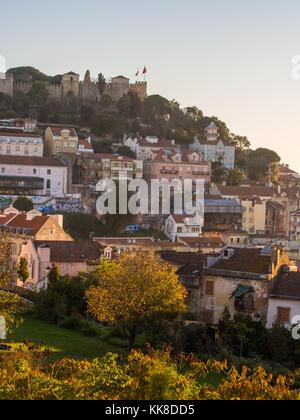 La soa jorge castle a Lisbona, Portogallo, con le case introno architettura, al tramonto. Foto Stock