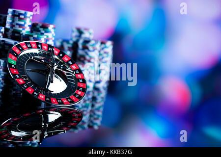 Casino tema. Alto contrasto immagine del casino roulette, poker, gioco di dadi, Poker chips su un tavolo da gioco, tutti su colorato sfondo bokeh di fondo.