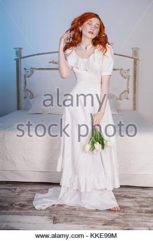Donna con rosso lungo i capelli ricci in bianco vintage abiti da sposa con il bianco perla orecchini sulle orecchie. Foto Stock