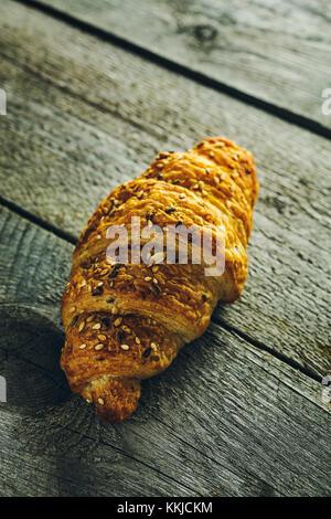 Croccanti croissant burroso con semi sul vecchio tavolo in legno Foto Stock