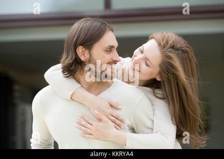 Giovane moglie abbracciando il marito dal suo retro godendo di uscite per il tempo libero Foto Stock