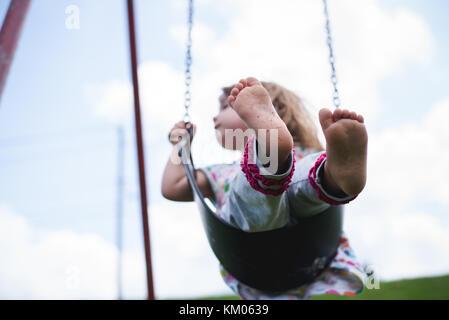 Una giovane ragazza oscilla su un altalena in un parco giochi a piedi nudi. Foto Stock