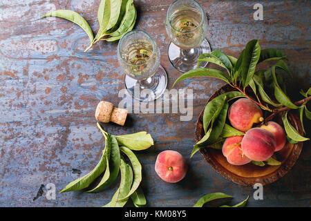 Le pesche sul ramo con foglie in ciotola di legno e due bicchiere di champagne con sughero sopra il vecchio sfondo Foto Stock